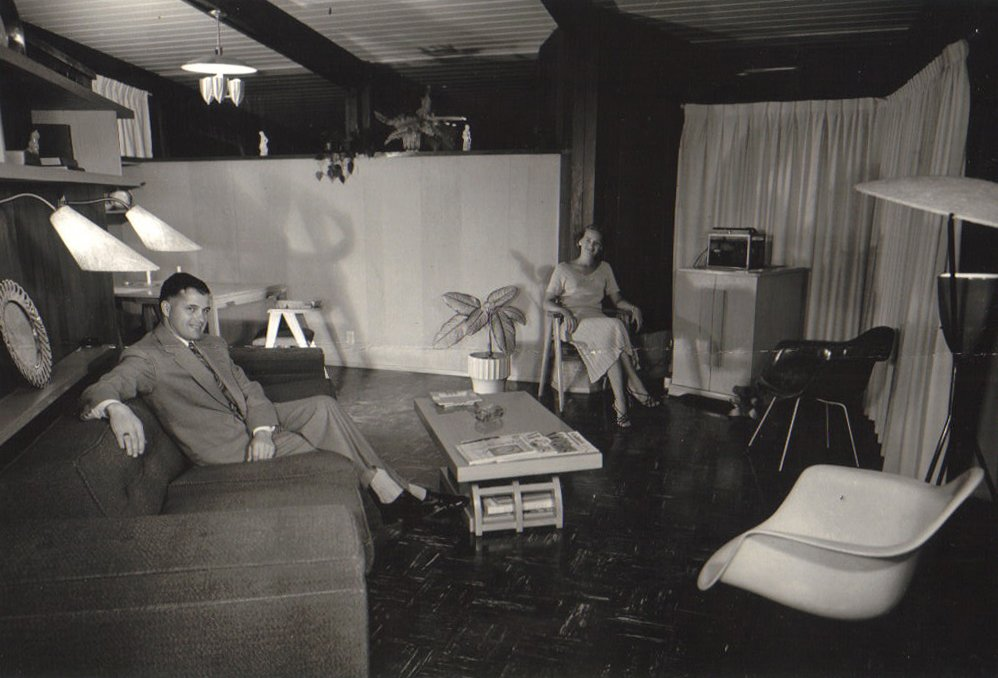 """Roy and Patricia Hamma enjoy time in their living room, furnished with Charles and Ray Eames pieces. Once the couple's MHA 111 model was complete, Roy Hamma, an attorney, hired a professional photographer to document their newly built home, which was one of the original 30 """"guinea pig"""" properties.  The MHA cooperative purchased 800 acres of land on the Brentwood side of the Santa Monica Mountains and worked with modernist architects A. Quincy Jones and Whitney R. Smith and structural engineer Edgardo Contini to build 350 homes. Only 85 houses from the original Jones/Smith plans actually saw the light of day.  A New Book on the Los Angeles Development of Iconic Modernist Architect A. Quincy Jones by Brandi Andres"""