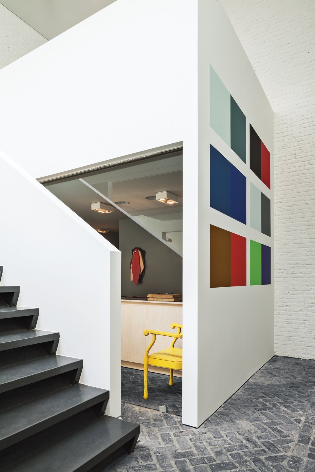 An installation by Willem Cole hangs in the gallery, which leads to an open stairway to the office and private bedrooms upstairs.  Photo 7 of 19 in This House Proves Art Galleries Can Be Super-Friendly