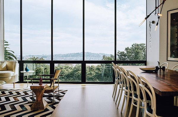 The living-dining room overlooks the neighborhood and the Bay beyond. The Safari chair was designed by Jens Quistgaard. Michael Thonet chairs are paired with a walnut table by Anthony Marschak for Original Timber Co.  Photo 7 of 19 in A Home with Eclectic Style Looks Just Right