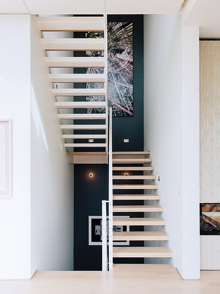 Across from the entrance is the main staircase, which leads to the bedrooms. Tagged: Staircase and Wood Tread.  Photo 8 of 19 in A Home with Eclectic Style Looks Just Right