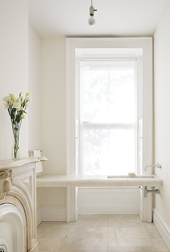 """Architects Anne Marie Lubrano and Lea Ciavarra limited the material selection in their renovation of a town house dating from 1899. The powder room on the first floor is located in a former waiting area (the previous resident used the level for his dental practice). It features a custom Alabastro marble sink and fixtures by California Faucets. The architects kept the original fireplace, paying homage to the structure's history. Benjamin Moore's Super White paint was applied to the ceiling and the White Dove hue to the walls. """"Positioning the faucets on the side wall emphasizes the horizontal,"""" Lubrano says. """"Wall-mounted fixtures feel less grounded and materials can continue uninterrupted below. We wanted the spaces to feel light, spacious and light-filled."""" Tagged: Bath Room, Marble Counter, Travertine Floor, Undermount Sink, and Ceiling Lighting.  Photo 1 of 7 in A Sophisticated Renovation of a 19th Century Manhattan Town House"""