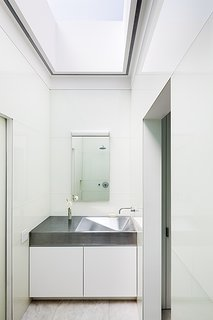 A Sophisticated Renovation of a 19th Century Manhattan Town House - Photo 2 of 7 - An angular brushed-stainless-steel sink and a painted plywood vanity in the third floor's master bathroom are custom. The general contractor built the vanity and comissioned the sink from New York's Master Restaurant Equipment. Back-painted glass panels by Bendheim clad the walls, and the fixtures are from California Faucets. Recessed lighting surrounds the perimeter of the Circle Redmont skylight, and the wall sconce over the Robern mirror is from Glashütte Limburg.