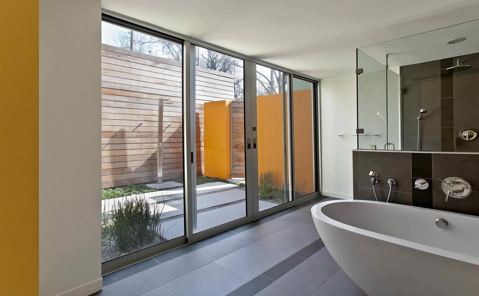 Nestled in between the master bedroom addition and the master bathroom is an outdoor shower. Just as with the kitchen and patio, floor-to-ceiling glazing and continuous concrete pavers blur the barrier between interior and exterior.