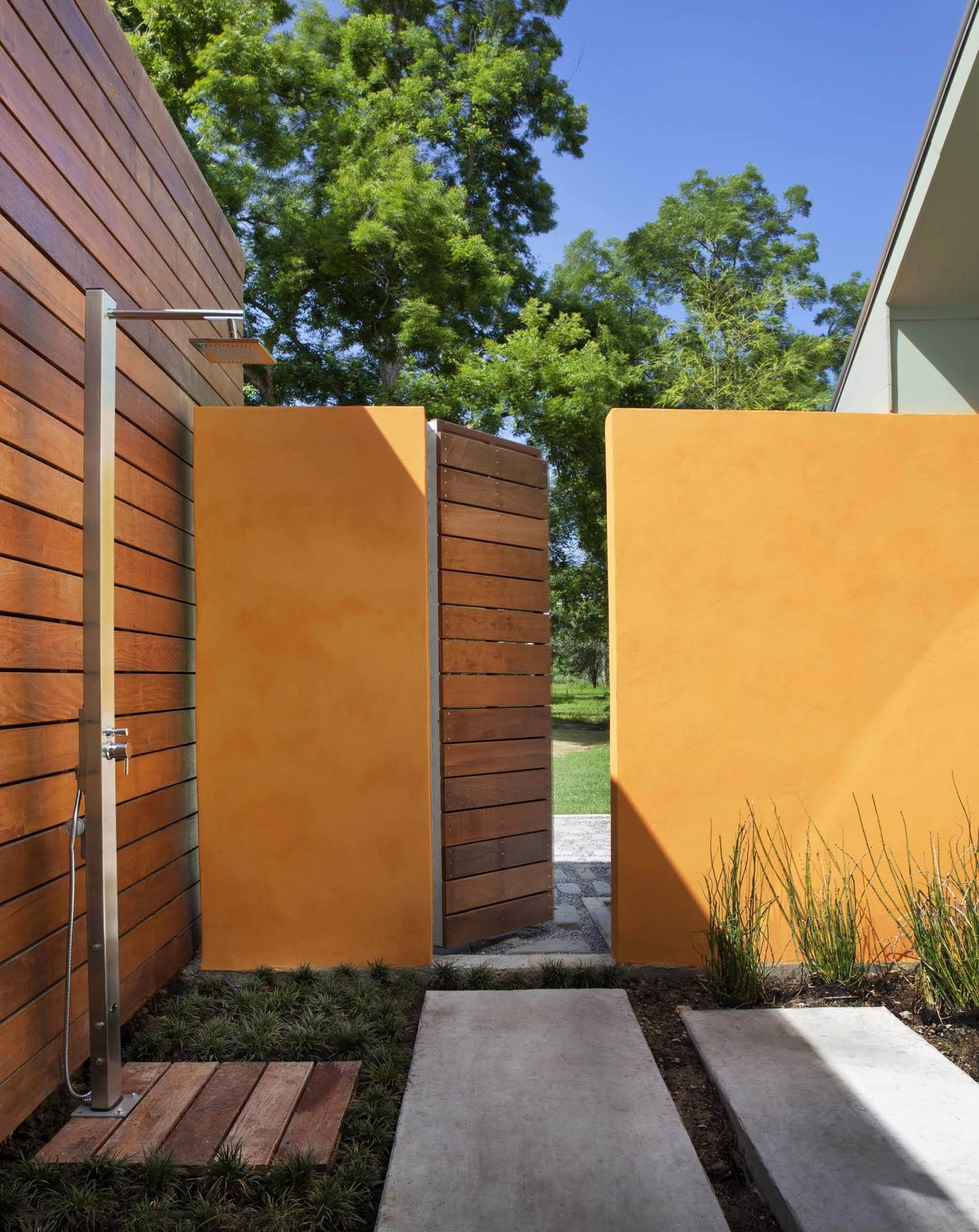 The shower offers a multisensory experience: the architect described how clients can take hot showers in the rain or simply lounge in the capacious garden area. Mint plants growing between the pavers release a pleasant smell when stepped upon.