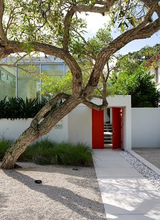 """This Sparkling New Home Is a Perfect Remake of Classic Sarasota School Modernism - Photo 5 of 13 - Benjamin Moore's Tomato Red provides """"punctuation"""" to the exterior. """"That was the cheapest way to have that hot spark of color,"""" Pirman explains."""