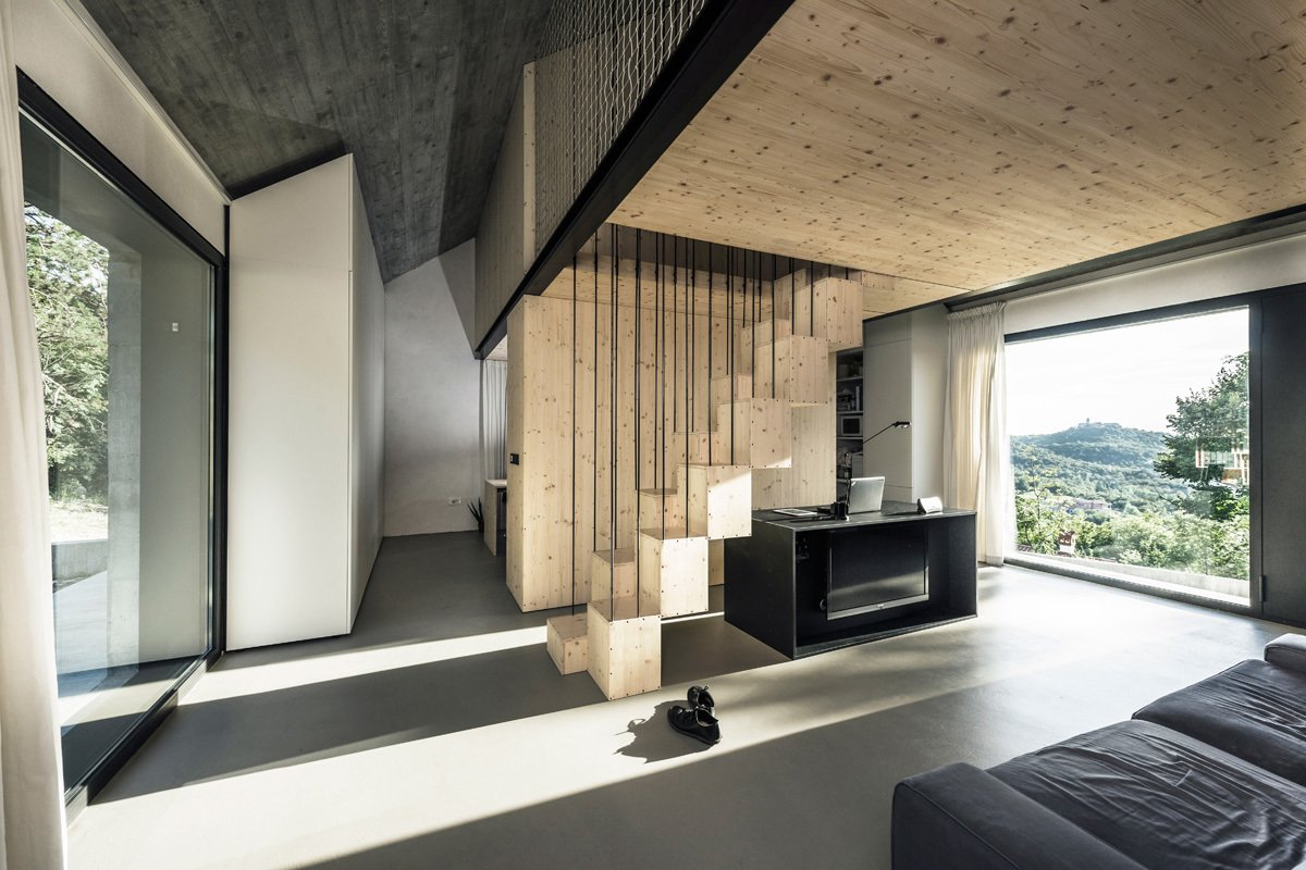 The kitchen, living area, and bathroom are located on the ground floor. Large windows overlook the surrounding forest, and Italy to the west.