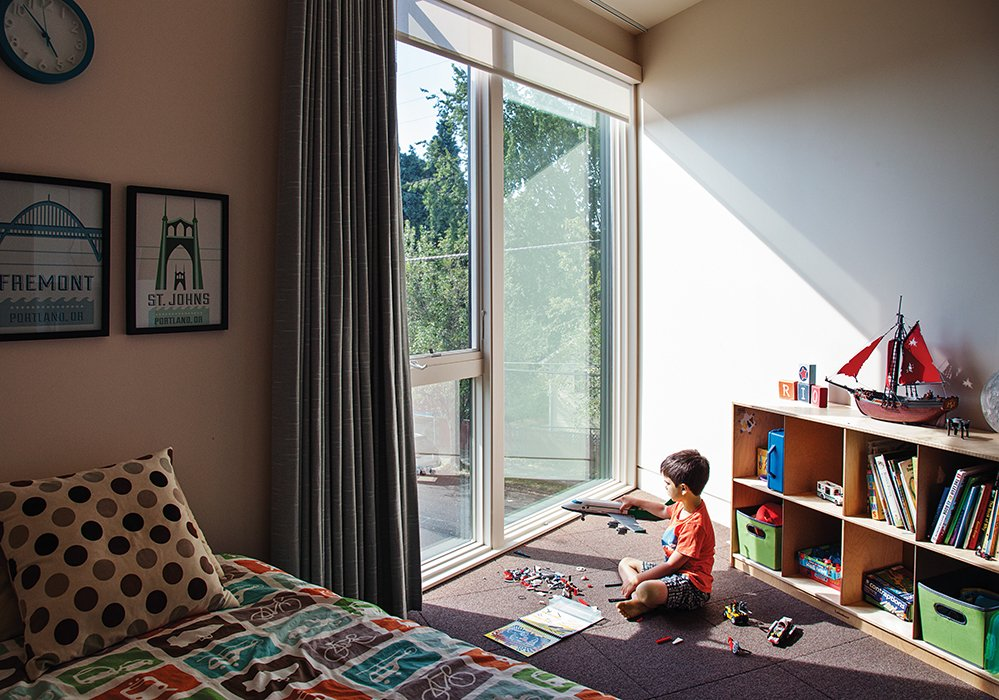"""There are floor-to-ceiling windows in almost every room,"" says Kaja Taft of her prefab home in Portland. ""Light was a big part of why we loved this design."" With so much light comes the need to block it out at times, especially in the children's rooms. Though the couple invested in solar shades and blackout curtains by Mari Design, ""They still get up at 5:30,"" Kaja says with a laugh. As in all the bedrooms, the carpet tiles are from Flor. Tagged: Kids Room, Bedroom, Bed, and Storage. 28 Triangles Make Up This Hyper-Angular Family Home - Photo 5 of 12"