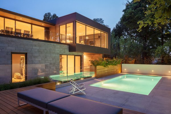 The cantilevered extension is clad in anthracide-colored concrete panels that reflect the limesone that was used to line the swimming pool. Photo 7 of Prince-Philip Residence modern home