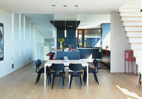 In the dining area, a Campo d'oro table from De Padova is ringed by vintage Michael Thonet Bentwood chairs. The kitchen features b3 cabinets by Bulthaup and custom stainless-steel countertops. The red Stool_One counter stools are by Konstantin Grcic for Magis.