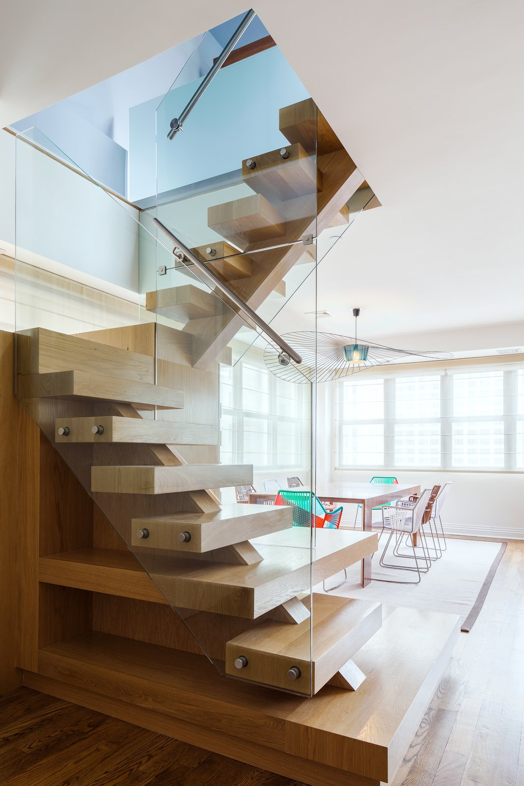 Reddy swapped out the spiral iron staircase for a modern wood one protected by glass walls. Tagged: Staircase, Wood Tread, and Metal Railing.  Lovely NYC Abodes That Will Give You Apartment Envy by Allie Weiss from Super Sleek Staircases