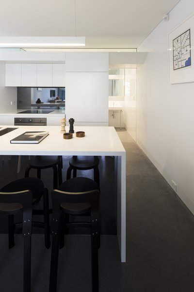 Casual meals are eaten at the kitchen's glacier white Corian countertop, which features Aalto K65 stools. The island's Blanco sinks offer a direct, uninterrupted sightline to the garden. Photo 5 of Cosgriff House modern home
