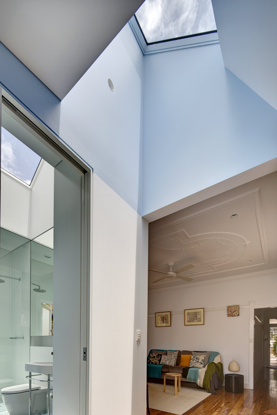 Save for a new fan and a coat of oil on its pine floors, the original living room remains unchanged. The master bathroom, however, has been completely refurbished with Scala accessories and a Duravit Happy D wall basin. Both rooms are brightened by skylights carved into the roof.  Photo 9 of 9 in Renovation Near Sydney Opens Home Onto a Lush Garden