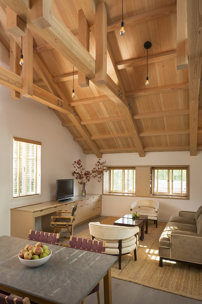 The redesign opened up the ceiling to reveal historic but damaged trusses, which were rehabilitated or replaced with Douglas fir depending on their degree of rot. The sofa and side tables below are from Mitchell Gold + Bob Williams. The desk chair is from McGuire.