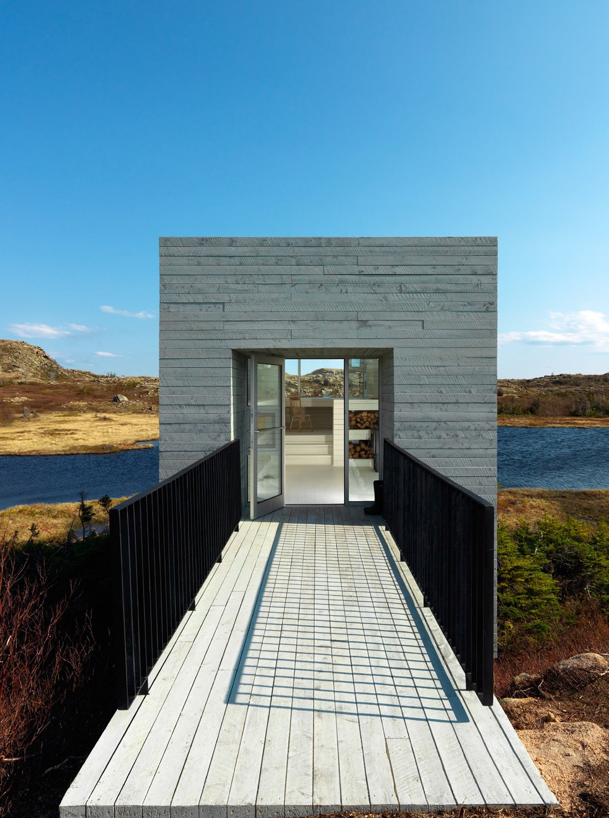 Those seeking isolation and inspiration to tackle their work need look no further. A minimalist cube set against a picturesque background form a studio free of distraction, except maybe that view! Newfoundland, Canada. By Saunders Architecture from the book Rock the Shack, Copyright Gestalten 2013. Tagged: Exterior, Wood Siding Material, and Cabin Building Type.  Best Photos from Stunning Waterfront Structures