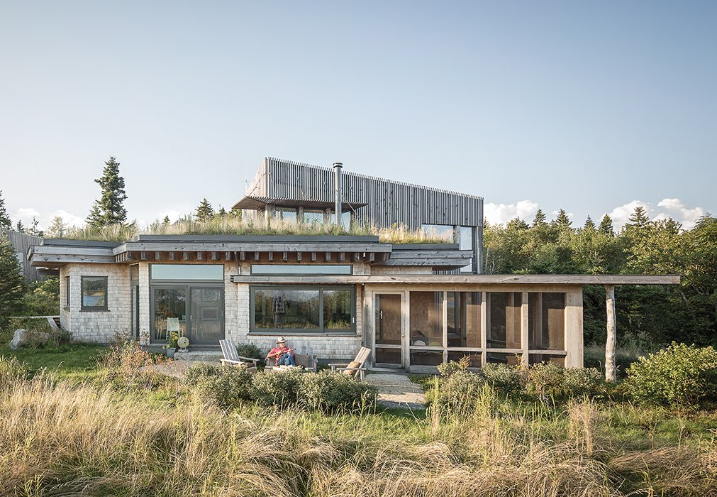 "Architect Will Winkelman and landscape architect Todd Richardson collaborated with a client, JT Bullitt, to design a house that blends into its surroundings in Steuben, Maine. The green roof gives the impression that ""the ground just jumped onto the roof,"" Richardson says. Tagged: Exterior, House, Wood Siding Material, and Green Roof Material.  Photo 1 of 7 in An Artist Builds a Wooden Home That Lets Nature Be the Boss"