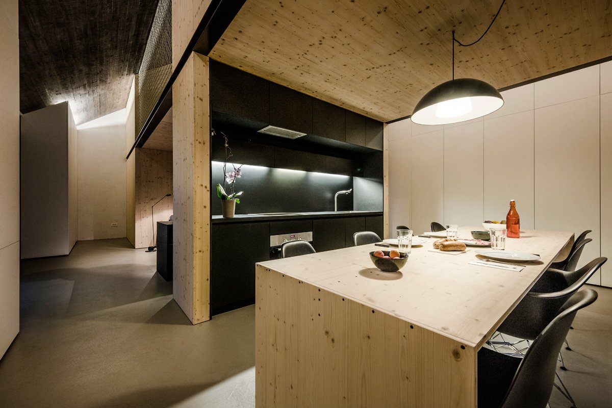 The kitchen uses laminated chipboard for the countertop and cabinets, and the same plywood used throughout the house for the table. The lamp is IKEA.  Photo 8 of 9 in Crazy Cool Loft Space Surrounded by Rope Walls from Open-Plan Dining Rooms
