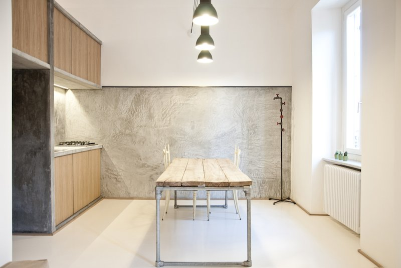 """It was supposed to be as naked as possible,"" says Alexandru Popescu, one of the members of R3Architetti who helped design and build the 3 Vaults apartment. ""The furniture is absolutely included in the architecture; it's more like an indoor landscape instead of a typical open plan."" The kitchen exemplifies their approach, with textured concrete walls contrasting with wood panels and salvaged industrial lighting. The table, custom built by R3Architetti, is made in part from pipes procured from one of their fathers, a plumber. Tagged: Kitchen and Wood Cabinet.  Photo 1 of 9 in Industrial Pied-à-Terre in Italy"