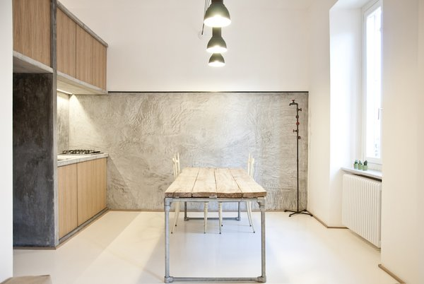 """""""It was supposed to be as naked as possible,"""" says Alexandru Popescu, one of the members of R3Architetti who helped design and build the 3 Vaults apartment. """"The furniture is absolutely included in the architecture; it's more like an indoor landscape instead of a typical open plan."""" The kitchen exemplifies their approach, with textured concrete walls contrasting with wood panels and salvaged industrial lighting. The table, custom built by R3Architetti, is made in part from pipes procured from one of their fathers, a plumber."""