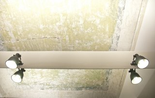 Industrial Pied-à-Terre in Italy - Photo 8 of 9 - A fading ceiling was preserved in the bedroom. Clear resin was applied to the blue and green pigments to freeze and preserve the aging wall.