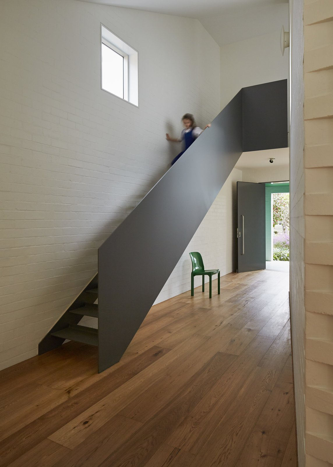 At the top of the steel staircase, a window-lined hallway wraps around the inner courtyard as it leads to the playroom. The upper level also includes the children's bedrooms and bathroom.  190+ Best Modern Staircase Ideas by Dwell from Riverview