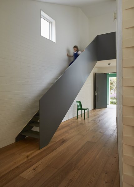 At the top of the steel staircase, a window-lined hallway wraps around the inner courtyard as it leads to the playroom. The upper level also includes the children's bedrooms and bathroom. Photo 3 of Riverview modern home