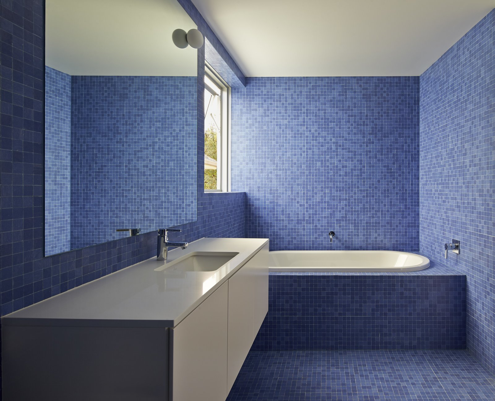 The bathrooms are tiled in bright blue mosaic to offset the home's limited materials and color palette. The sinks, toilets, and tubs are by Villeroy & Boch, while the faucets and towel rails are by Grohe and Avenir, respectively.  Photo 1 of 13 in 12 Creative Ways to Use Tile in Your Home from Riverview
