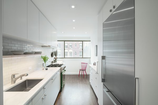 The homeowners, avid cooks, worked with a design duo and a contractor found on the site. To make the kitchen seem larger than it is, the team decided to place the largest cabinets and appliances near the entryway, with less clutter toward the window.