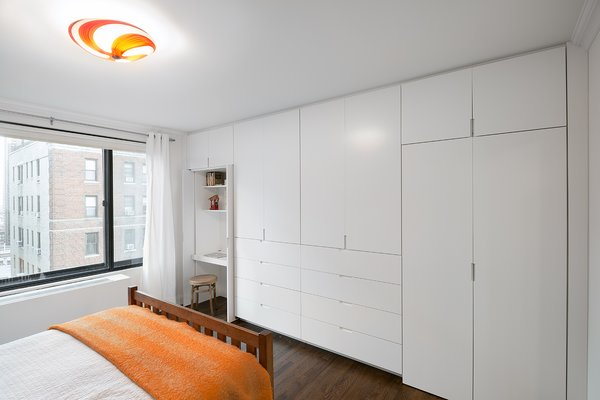 A custom unit with handleless, lacquered doors conceals a small workspace and ample clothes storage.