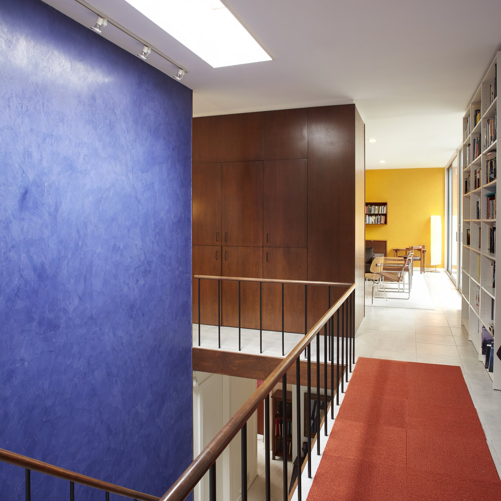 The interiors of Hugh Smallen's 1963 Becker House are accented by a rich blue that connects the two levels, while a vibrant yellow draws attention towards the living room.  Photo 11 of 15 in Get Ready For July 4th With 15 Spaces That Rock Red, White, and Blue from Beloved Midcentury Houses Examined After Decades of Wear and Tear