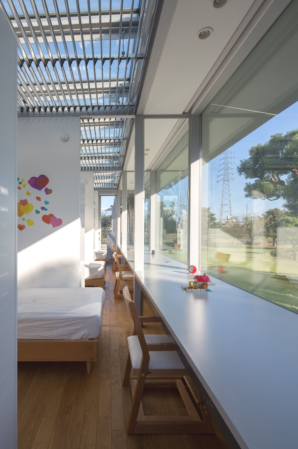 The girls' bedrooms are partitioned by sliding screen panels, which can be opened for access or shut for for privacy. Each room enjoys a stunning wall-to-wall exterior view. Tagged: Kids Room and Bedroom.  Bedrooms by Dwell from A Green House in Japan Sets the Stage for Family Time