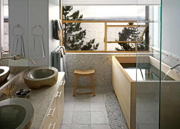 "Grace Boyd's favorite room has a stunning view of Puget Sound reflected in the Hinoki tub she had custom-sized by Roberts Hot Tubs. The clean lines of soaking tubs ""work well in conventional bathrooms,"" says Roberts' Andrew Harris, ""no need to make the whole room Japanese-style."" Grace echoed the grey of the sea and sky in the sinks and the silvery pebbles around the tub. After 32 years in West Seattle, she asked architect Mark Travers to build her a new house in the same spot- she couldn't bear to lose her view. Tubs are popping up in real estate listings as a selling point; new owners can have an existing tub sanded to reveal a fresh layer of pristine scented wood. Photo courtesy of: Roberts Hot Tubs Japanese Soaking Tubs - Photo 7 of 13"