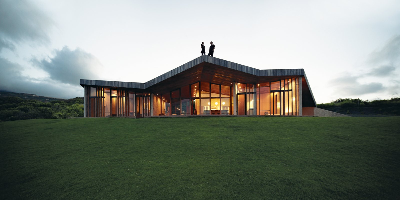 """We sought to create a house that would not damage the environment and not be too visible,"" says architect Tina Gregorič. A single zigzagging roof stretches over 5,380 square feet, doubling the area of the interior spaces and serving as an ideal spot for sunset cocktails and whale-watching. Tagged: Exterior, House, and Wood Siding Material.  Photo 4 of 10 in Clifftop House with Angled Roof in Maui"