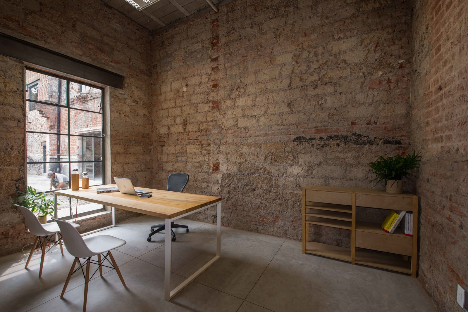 The firm added some windows to direct attention to the interior garden area. Eames shell chairs and an Aeron chair from Herman Miller surround a custom desk.  exposed brick by Kate Reggev from Modern Office Space Carved Out of a Crumbling Brick Building