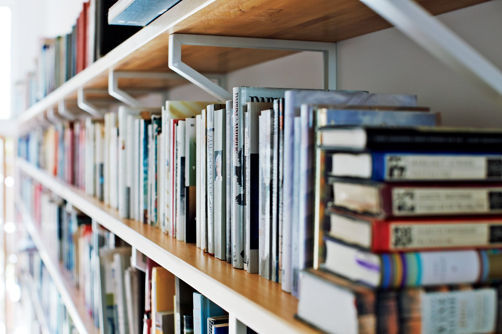 Sawatzky designed the bookshelves along the living room wall out of Ikea components: one-inch Lagan butcher block countertops and inexpensive Ekby Lerberg brackets. She also used pieces of the strong and attractive countertops for built-in shelves in the upstairs lounge as well as for trim in the kitchen.  Photo 6 of 11 in Don't Let the Sign Fool You, This Old Storefront is a Home