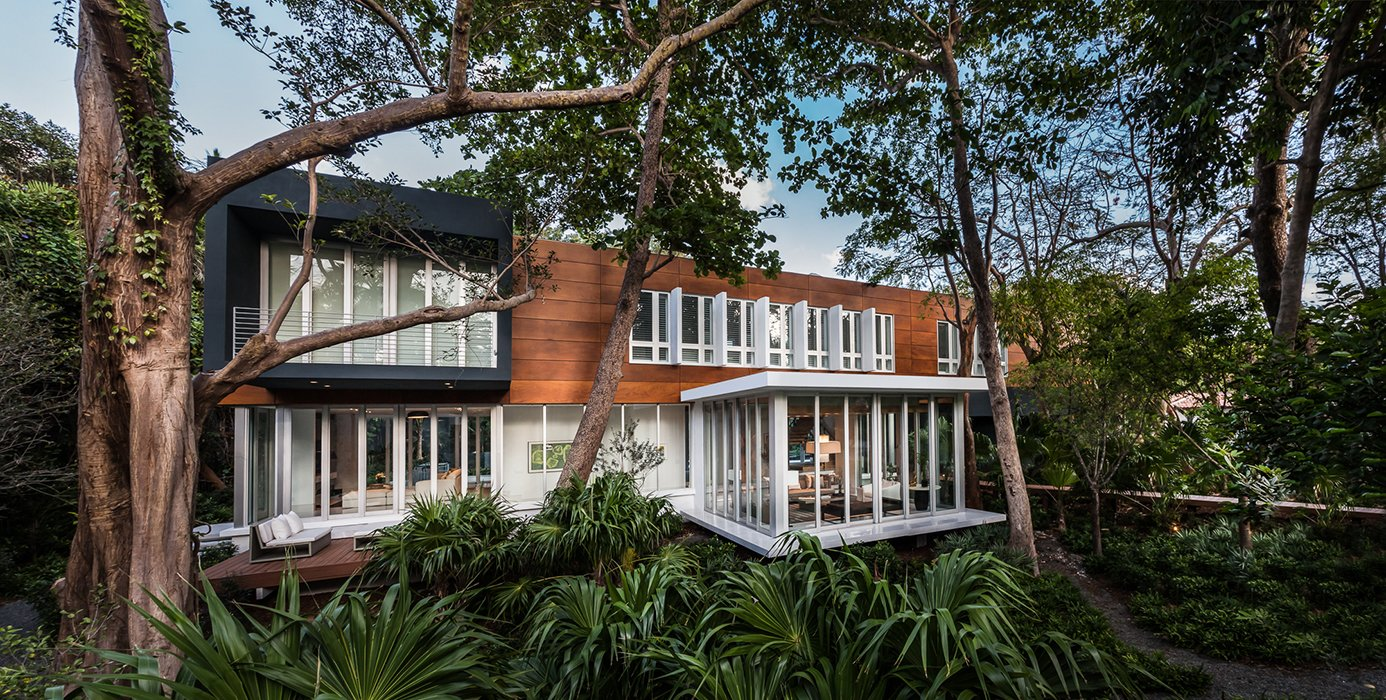 The house is located in the Camp Biscayne area of Coconut Grove, a neighborhood in Miami. Its main volume is clad in Prodema. Tagged: Exterior, Stucco Siding Material, Wood Siding Material, and House.  Photo 1 of 12 in This Modern Miami House Feels Like It's in the Middle of the Jungle