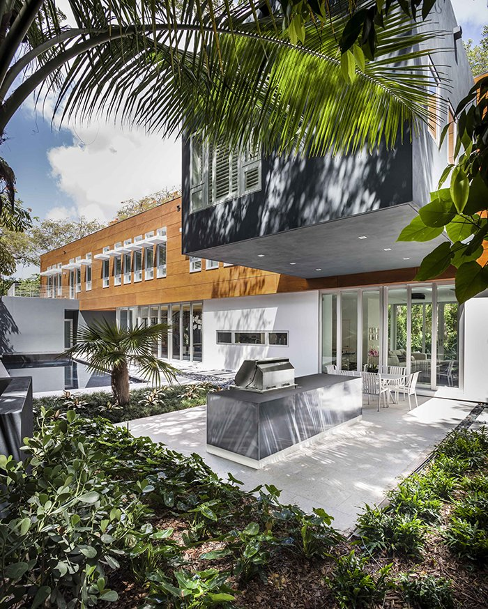 An elegant pool and outdoor kitchen extend from the living areas.  Photo 5 of 12 in This Modern Miami House Feels Like It's in the Middle of the Jungle