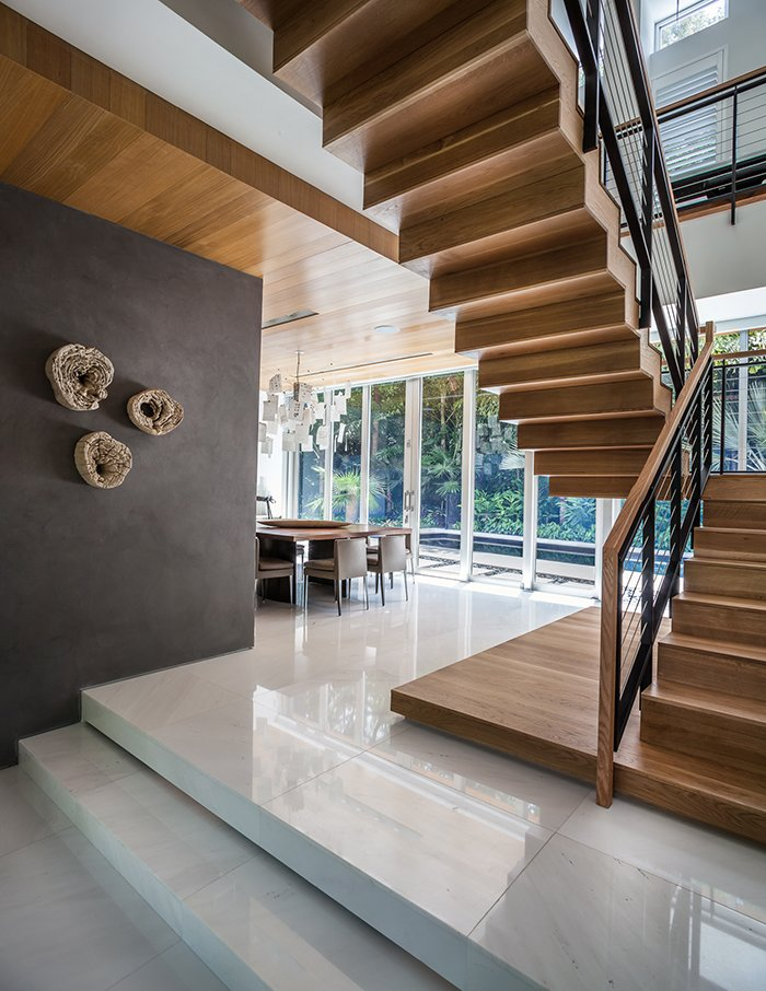 The ground level contains the living and dining spaces. Upstairs there are two bedrooms, plus the master suite. This Modern Miami House Feels Like It's in the Middle of the Jungle - Photo 7 of 12