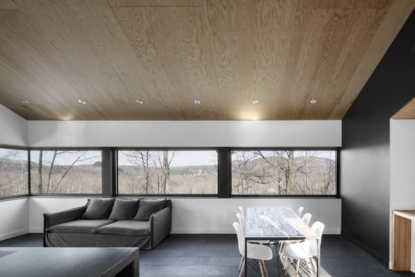 """The horizontal strip window in the combined living and dining room frames the wooded mountain range and valley, transforming the home's interior with the changing seasons. It also saved money during the construction process, as the minimal glazing cost a lot less than floor-to-ceiling windows. """"It lets you enjoy the spectacular views without breaking the bank,"""" Dworkind says. Tagged: Living Room, Sofa, and Chair.  Photo 3 of 11 in Amazing Cantilevered Home in the Mountains"""