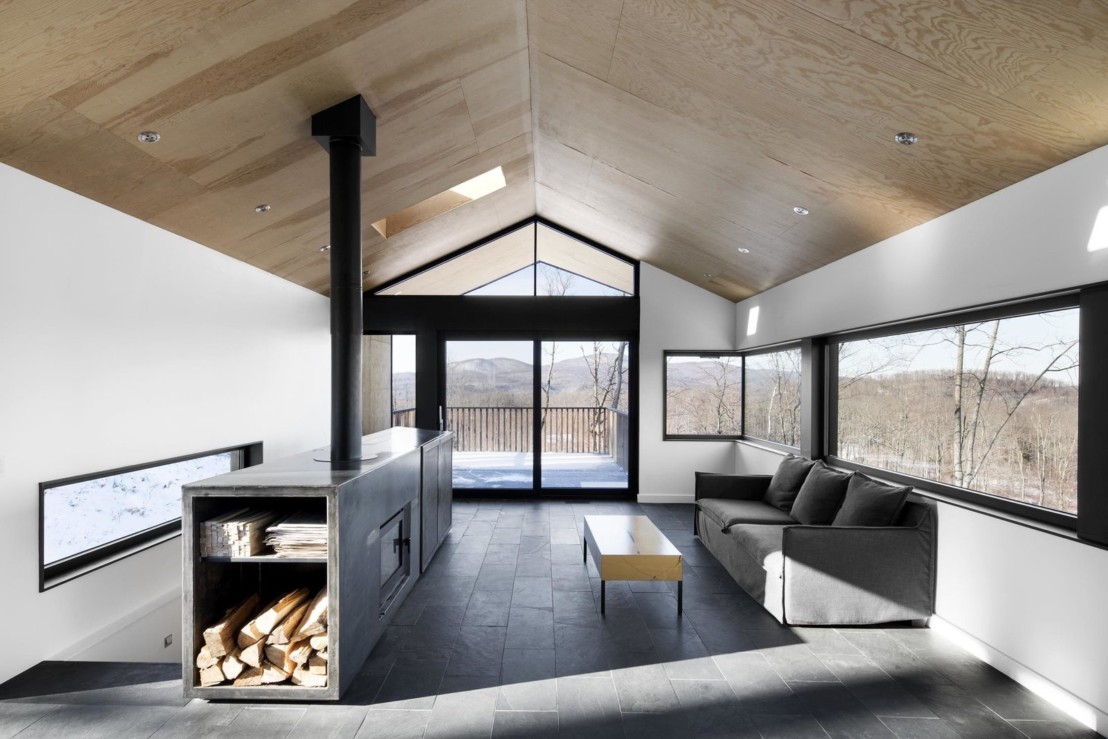 A centralized fireplace was built into a custom, multi-purpose cabinet welded from sheets of hot-rolled steel. It stores firewood, holds a TV, and even acts as a guardrail for the staircase. Tagged: Living Room, Coffee Tables, Recessed Lighting, Sofa, Cement Tile Floor, and Wood Burning Fireplace. Amazing Cantilevered Home in the Mountains - Photo 4 of 11