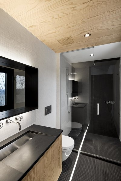 In the bathroom, the architects mounted a Kohler sink on a sloped, custom-slate countertop. Since the stone doesn't hold up well in water, the architect switched to black mosaic tile in the shower. The faucets are from Cabano's Century series.