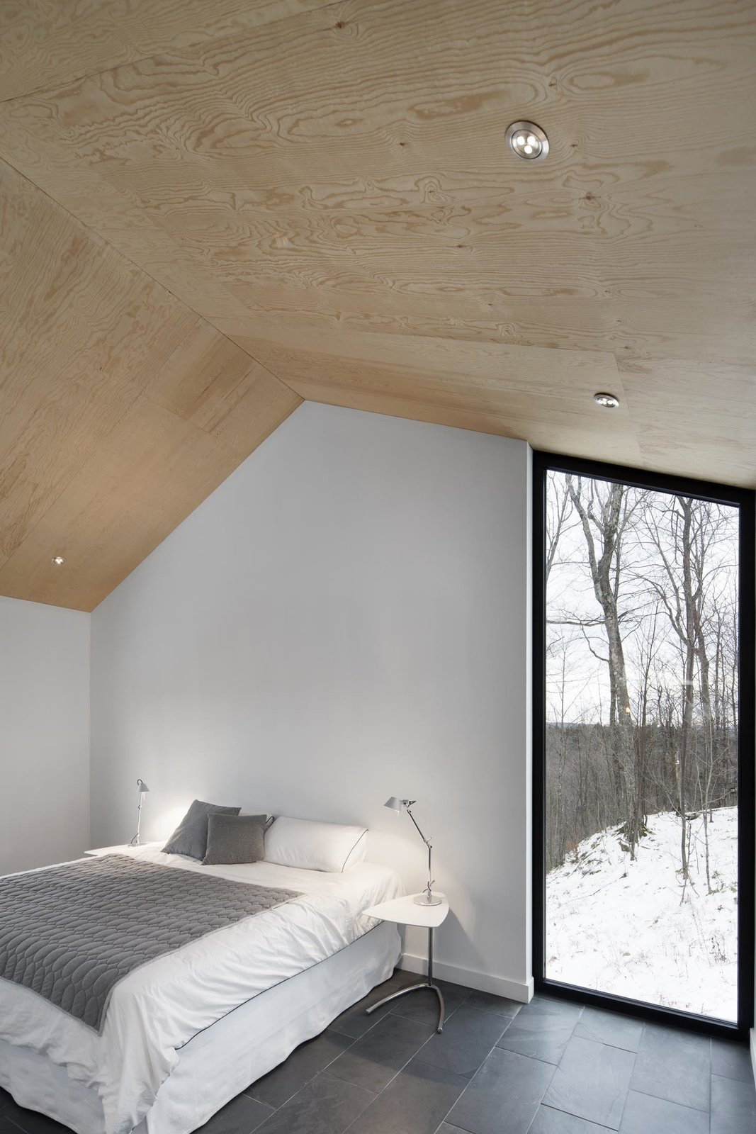 The bedroom's vertical, floor-to-ceiling window lets occupants admire the graceful trees outside. A Mini Tolomeo lamp by Artemide sits on the bedside table. Tagged: Bedroom, Table Lighting, Bed, and Slate Floor.  Photo 9 of 11 in Amazing Cantilevered Home in the Mountains