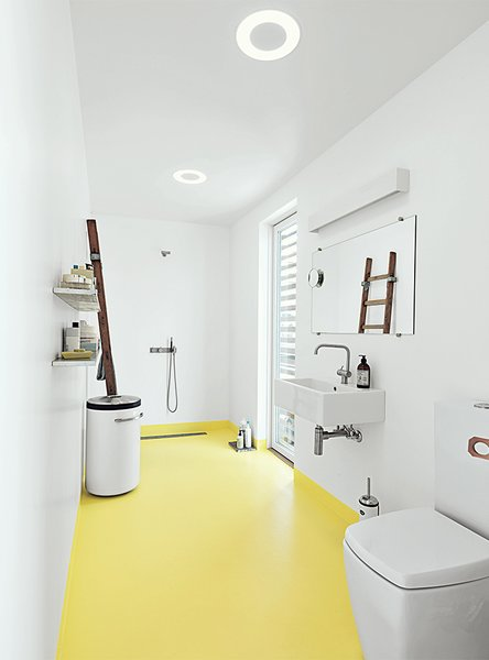 In the bathroom, the home's epoxy floor transitions from whitish gray to submarine yellow. The sink and tub are by Galassia, and the faucets are by Vola. A ladder, which serves as a towel rack, was sourced from the Danish Emergency Management Agency. The black-and-white industrial laundry bin is by Vipp.