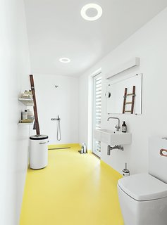 Each Day at This Floating Home Begins With a Swim, Just Two Feet From Bed - Photo 8 of 9 - In the bathroom, the home's epoxy floor transitions from whitish gray to submarine yellow. The sink and tub are by Galassia, and the faucets are by Vola. A ladder, which serves as a towel rack, was sourced from the Danish Emergency Management Agency. The black-and-white industrial laundry bin is by Vipp.