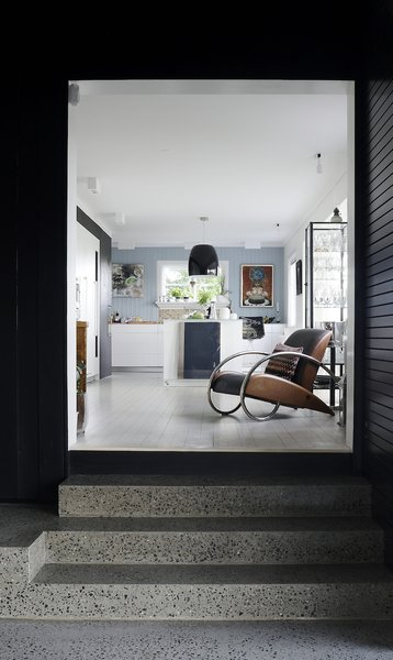 The owners, a couple who work at home, clamored for more space with the new addition. Solbjør created dramatic entrances, such as these stone steps leading into the kitchen, to heighten the contrast between the old and new. Photo 3 of Charred Cedar modern home