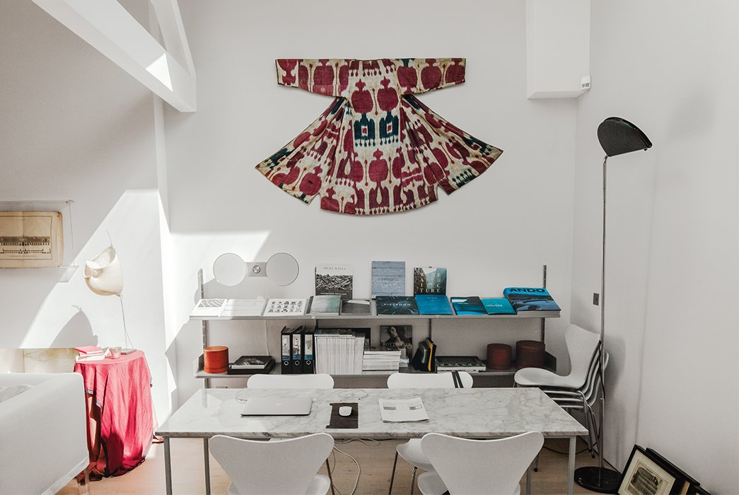 Above the 606 Universal shelving by Dieter Rams for Vitsœ, Molineus displays a Central Asian ikat wedding garment that dates to around 1900. The Gaku floor lamp at left is by Dagmar Mombach and Ingo Maurer.