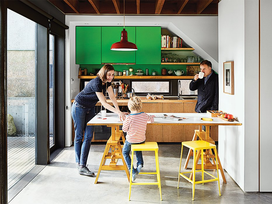 The family selected a Leonardo table by Achille Castiglioni to serve as additional countertop space. Waddell made the cabinets with a friend. Tagged: Kitchen, Wood Counter, Accent Lighting, Colorful Cabinet, and Concrete Floor.  Photo 5 of 11 in This Bungalow is Anything but Basic