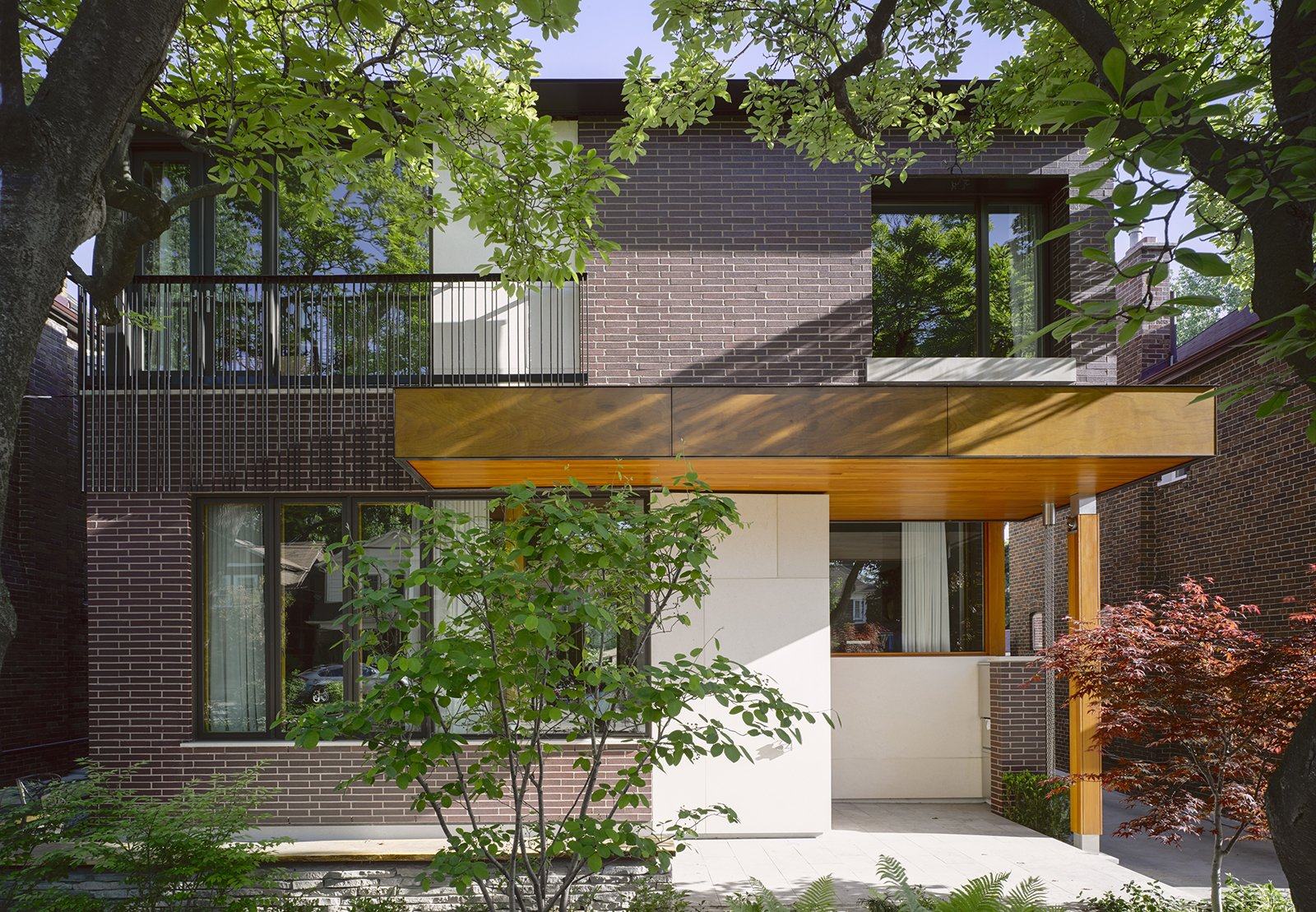 Located in Toronto, the Bedford Park House embodies an architectual hat trick: it's smart from a technological standpoint, it's energy efficient, and it's designed so the residents, a doctor and his wife, can age in place. Architect Alex Tedesco, a senior partner at LGA Architectural Partners, created a thoughtful design grounded in the advanced building science and that embodies the principles of modernism. The facade is clad in Rum Raison Velour brick by Belden with Douglas fir accents.  Photo 1 of 11 in Smart Tech Makes this Modern Home Ultra Energy Efficient