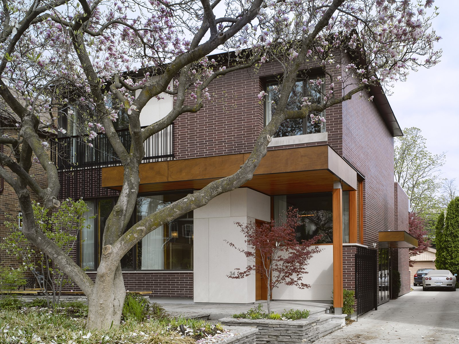 """The house responds to its site. """"The design was directly influenced by two mature, century-old magnolia trees in the front and a Japanese maple in the rear,"""" Tedesco says. """"The location of widows and main program spaces, such as the living room and master bedroom, were strategically placed to take full advantage of views of these trees. Because the trees are fully visible from the interior, seasons and the trees' yearly blooming cycles play a significant role in daily life—they're not just landscape elements. The window sizes and their locations were coordinated with the existing trees to take advantage of passive solar shading in the summer and solar gain in the winter months when the trees do not have foliage."""""""