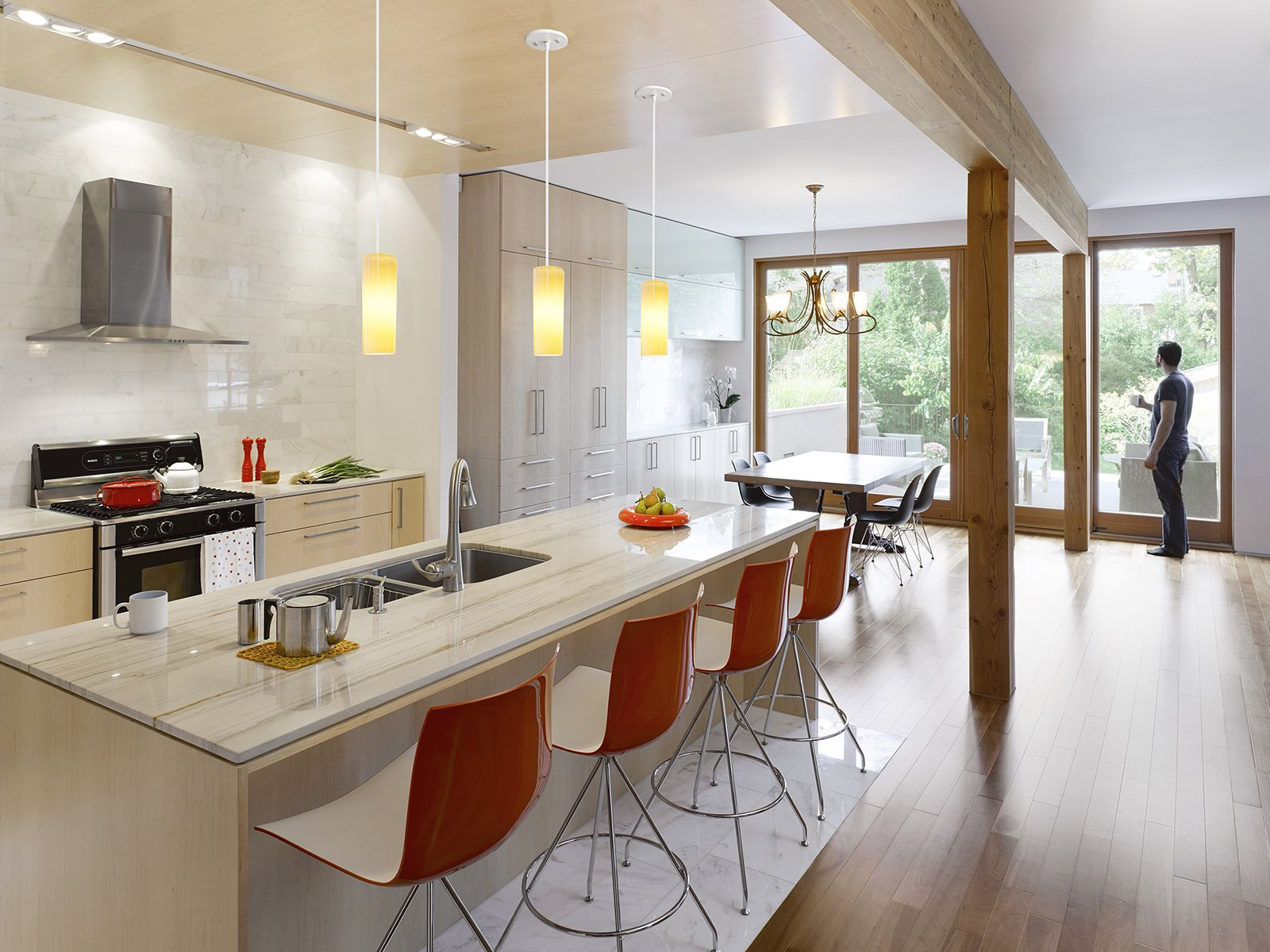 "The kitchen is outfitted with a duel-fuel range by Bosch, a Diamonte Canopy hood by Faber, a LaPerla dishwasher by Miele, French-door refrigerator by LG, Blanco sink, and Compact Smart overn by Breville. Catifa 46 stools by Arper are stationed at the bar. The counters are quartz and the cabinets are solid maple. ""Given that the owners' intention was to stay and age in the house, we decided that the materials needed to be elegant and timeless and, in essence, could also age well in place,"" Tedesco says. ""This led to devising a refined and warm palette of natural finishes. White carrara marble, oiled clear Douglas fir, and maple floors and millwork create a light, warm interior with a reddish hue that emanates when the sunlight washes the woods. The selection process included R-and-D on the materials to assess their ability to be both robust enough to handle every day wear and tear in the short term and acquire a beautiful patina long term. We also researched MSDS charts to ensure they were safe, non-toxic, and would not off-gas.""  Photo 4 of 11 in Smart Tech Makes this Modern Home Ultra Energy Efficient"