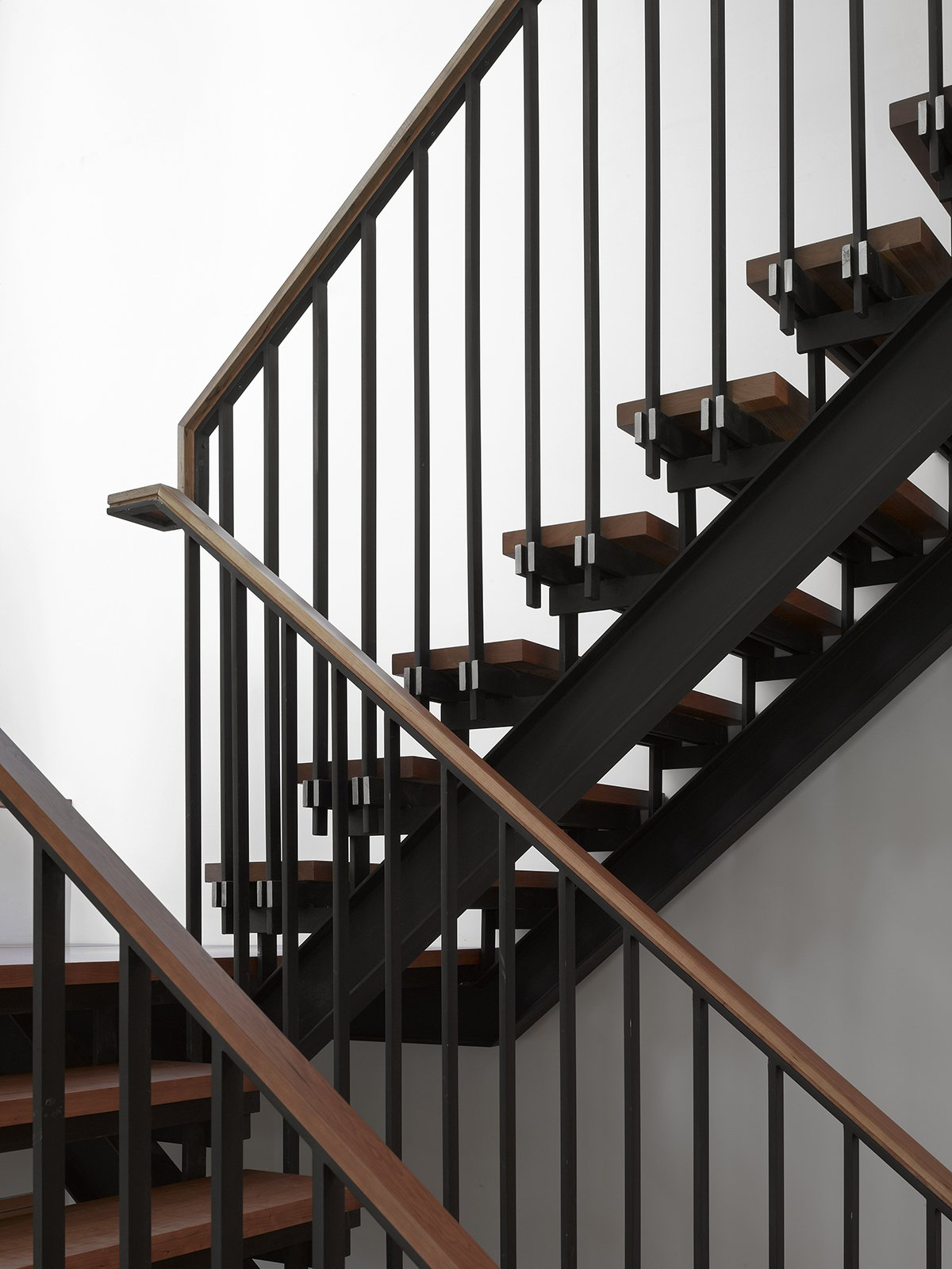 Tedesco's father was a precision machinist and his uncles worked as welders and carpentry framers. As a tribute to his family's history, Tedesco made the blackened-steel-and-wood staircase a focal point—it can be seen from nearly every room in the house.  Photo 6 of 11 in Smart Tech Makes this Modern Home Ultra Energy Efficient
